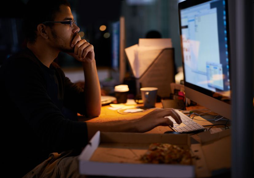 Shot of a young programmer working in a dimly-lit office. All screen content is designed by us and not copyrighted by others, and upon purchase a user license is granted to the purchaser. A property release can be obtained if needed.