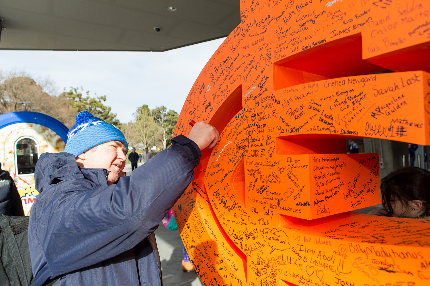 Supporters write their names on the CARLTON RESPECTS monogram to pledge their support for respect and equality.