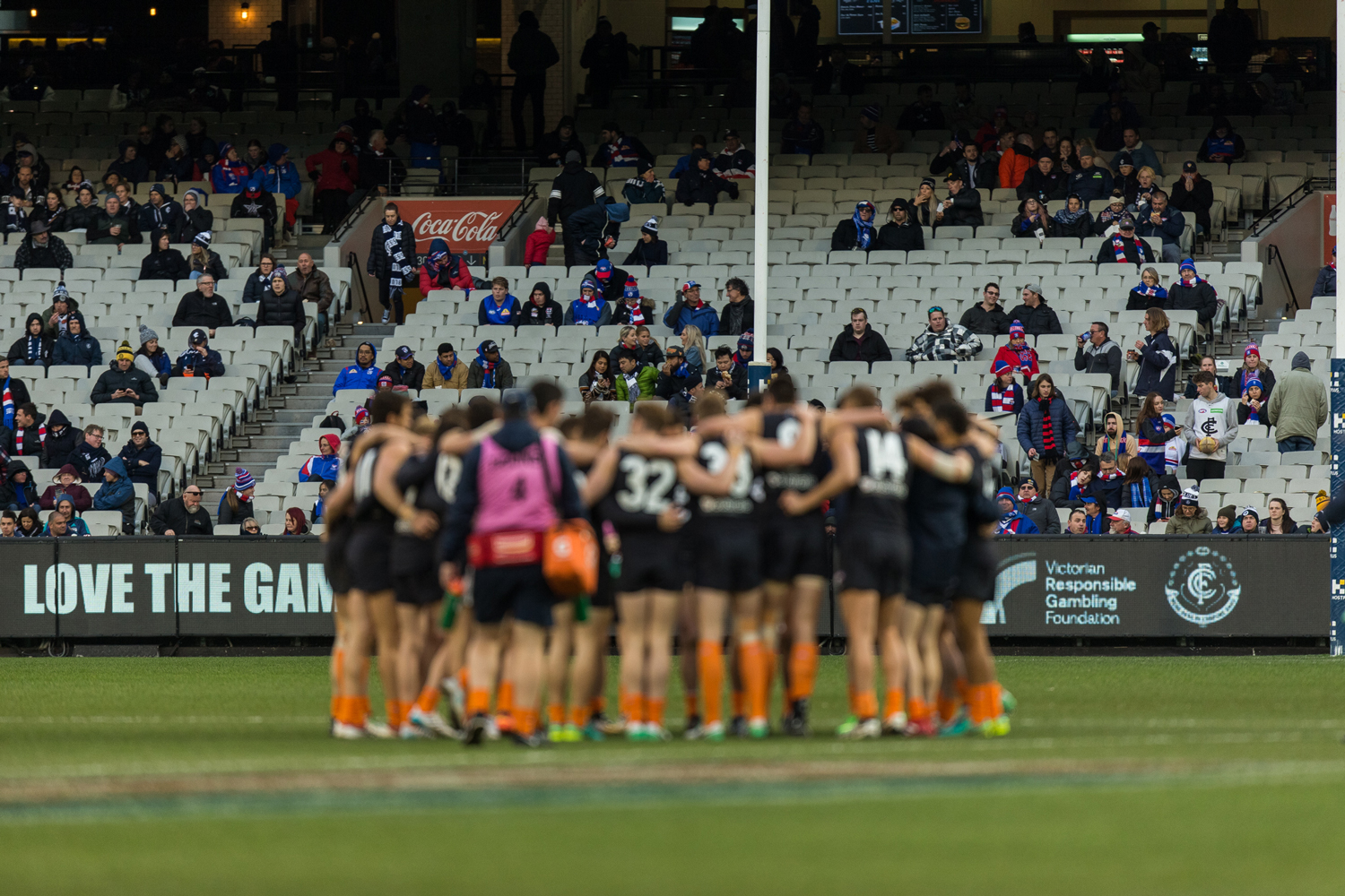 The players huddle in the middle of the ground before the first bounce of CARLTON RESPECTS round