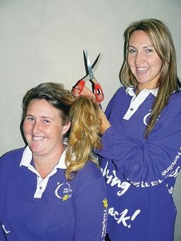 Lucy Lang (seated) and her sister Emma Walton stage a hair-cutting pose in preparation for WA Cancer Council's Relay for Life event.