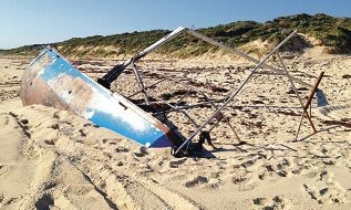 The Thetis II lies on Eglinton beach with half its hull submerged in sand and the mast now broken.