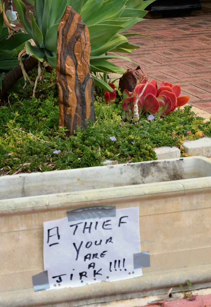 The sign left on the pot plant. Picture: David Baylis.
