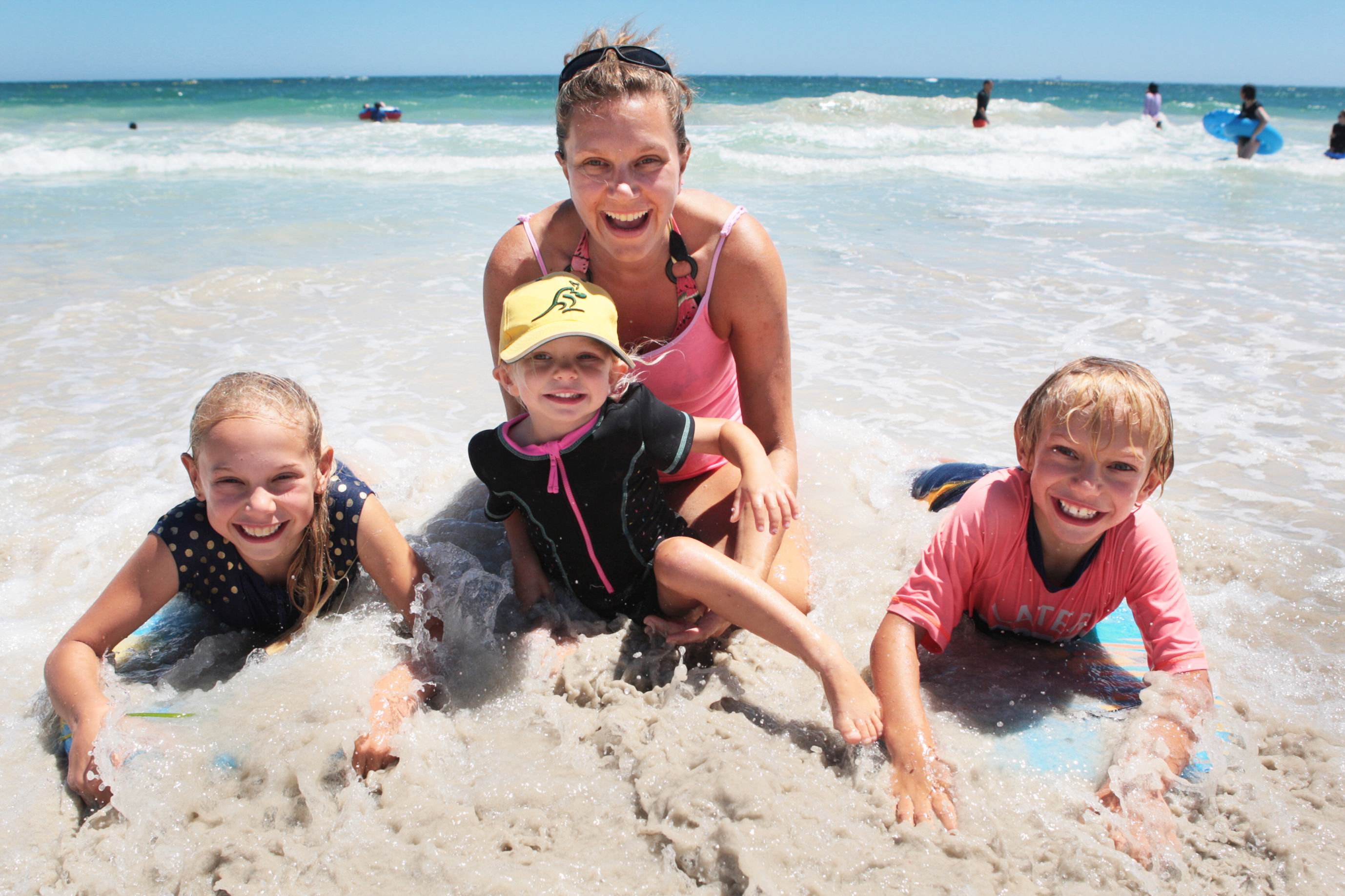 Louise Skipworth with her children Olivier, Millie and Harry, enjoying the surf at Sorrento's shark-protected beach. Picture: Bruce Hunt d463985