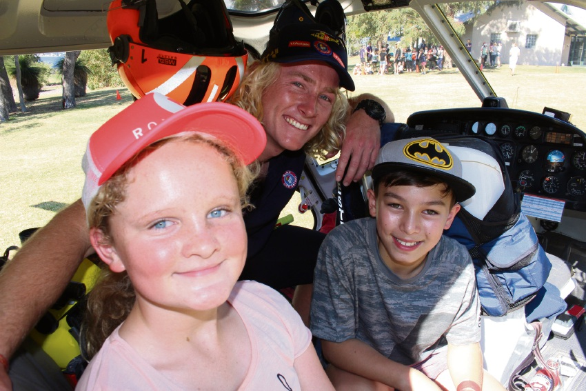 Eleven-year-olds Marnie Griffiths and Jaemon Yam check out the Westpac Rescue Helicopter with rescue swimmer Nick Wagstaff.