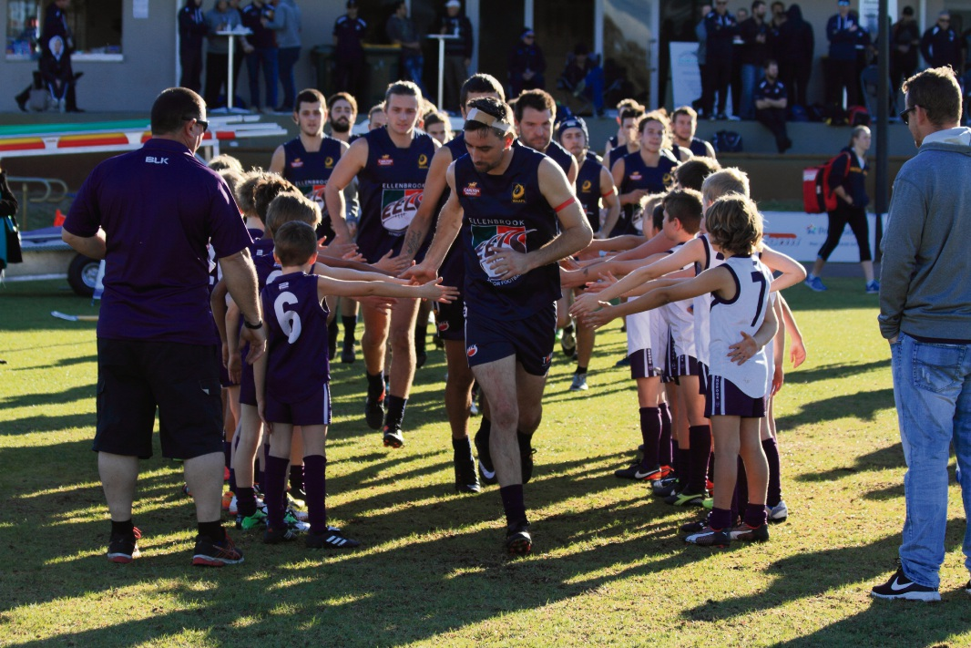 Captain Matt Craig leads his team on to the field, well supported by junior players.
