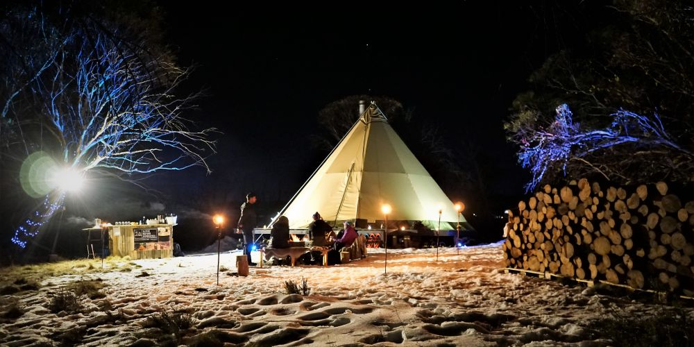 A teepee settled in the snow on Mount Hotham, as part of the Alpine Nature Experience. Guests hike out on snowshoes and enjoy mulled wine around the fire before making authentic French fondue inside.  Photo: AAP