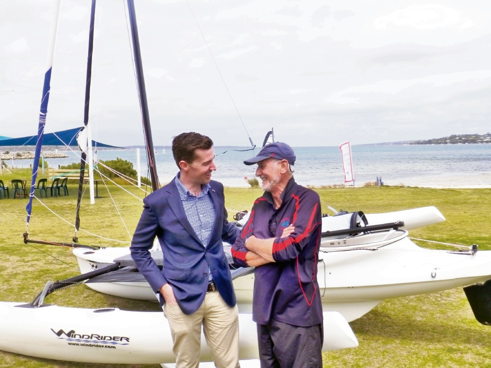 Dawesville MLA Zak Kirkup and John Hunt discuss the feature of the trimarans used to support the Sailability program.