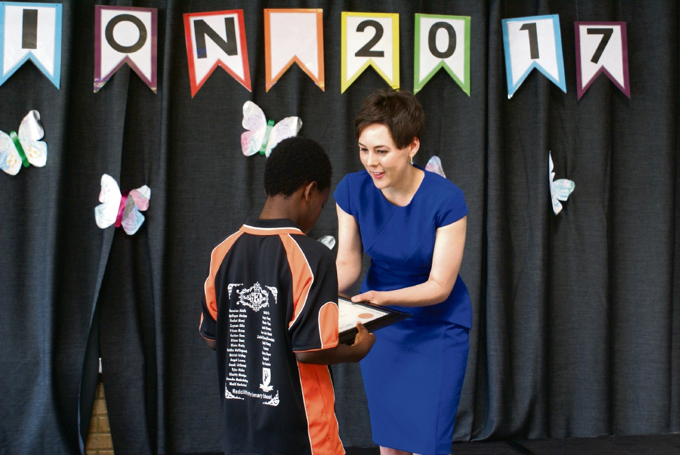 Belmont MLA presents a scholarship to Odrick Irishuye at his graduation assembly at Redcliffe Primary School.