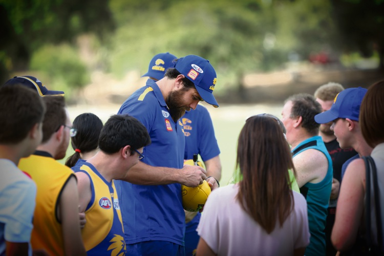 Josh Kennedy signing some footballs. Picture: Andrew Ritchie.