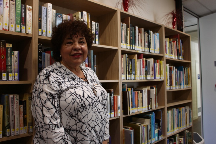 Nilda Eisen with foreign language books in Umbrella Multicultural Community Care Services library.