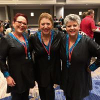 Helen Bolton, Lions Gate Chorus director Sandy Marron and Kali Caramia.