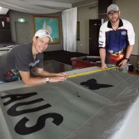 Beldon resident Colin Spence (right) with an assistant measuring a Moth class sail being used in the World Championship Series being held on the Swan River this week.