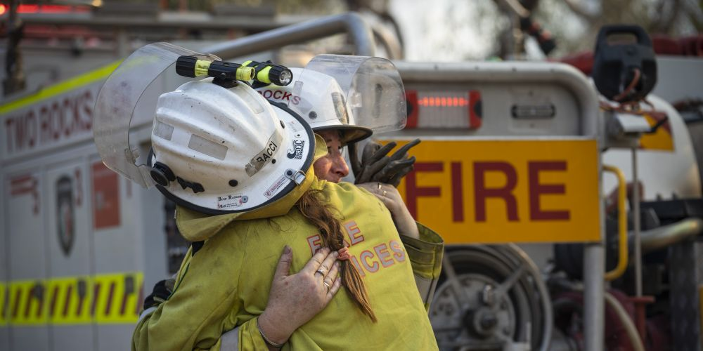 Firefighters hug each other during the December fire. Picture: DFES incident photographer Evan Collis