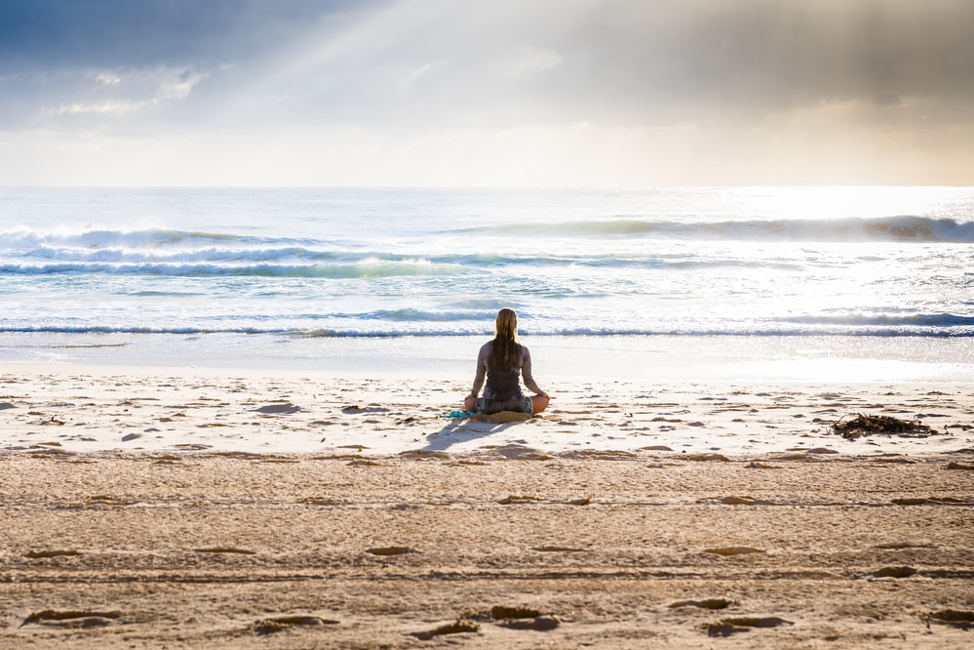 woman doing yoga at the beach by herself photo by simon rae @ unsplash.com