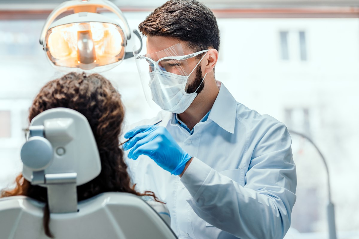 Male Dental Practitioner with brown hair, a mask and clear visor is looking at a female patient with brown curly hair who is sitting in a white dental chair.