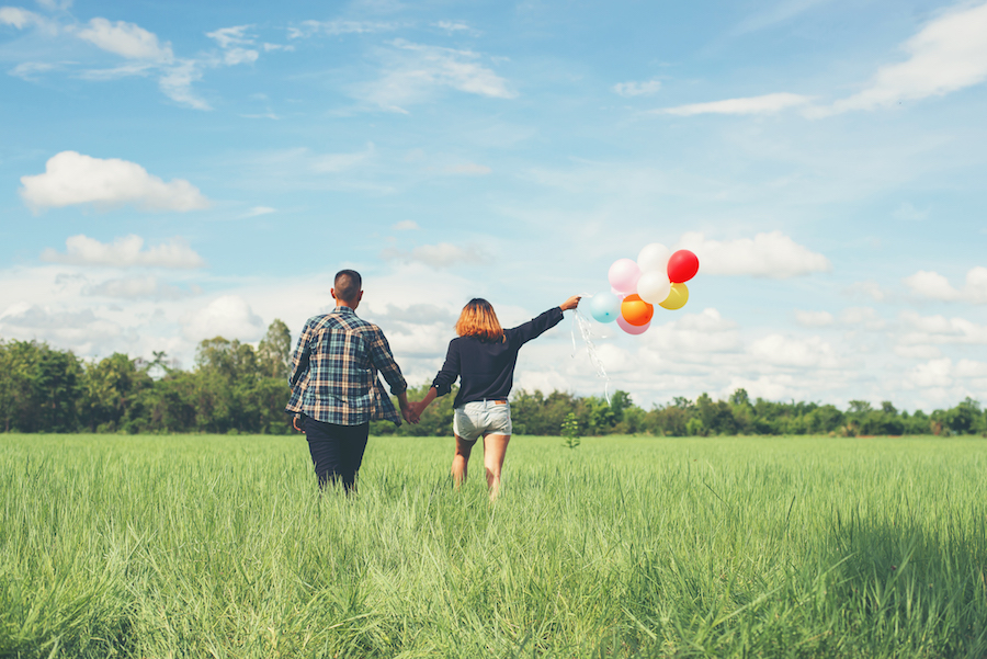 Back of happy young asian couple holding balloon and walk together on green grass.