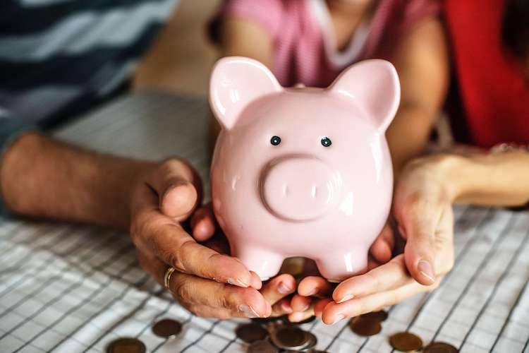 Lady holding pink piggy bank
