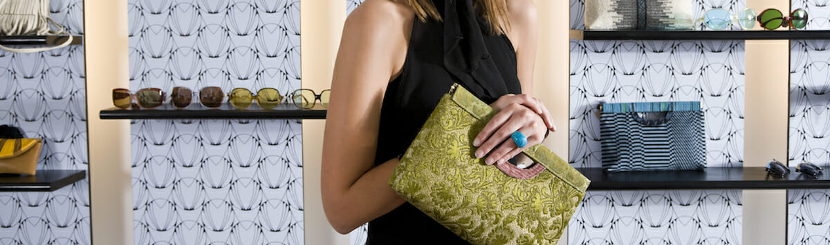 Shopper, young woman in her 20s, in retail store holding purse