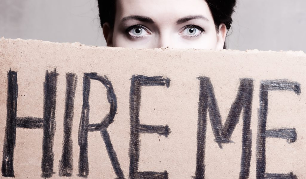 Woman peeking over a sign which says 'hire me'