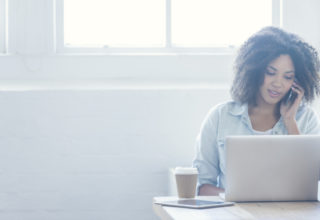 Woman working on a laptop while on phone.