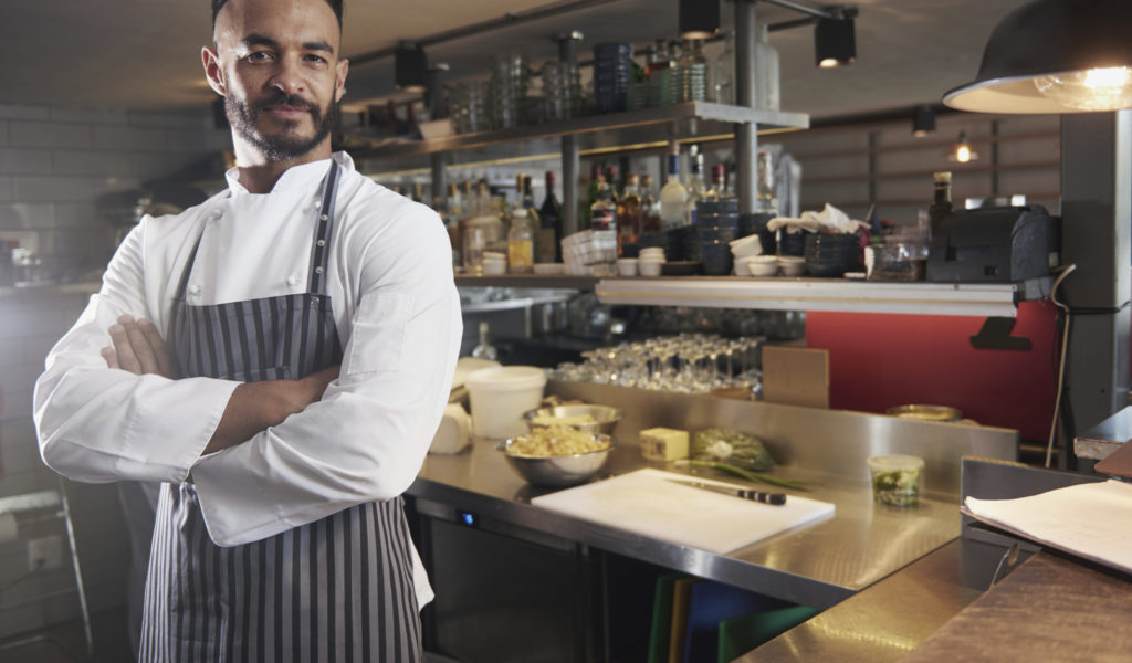 Cropped portrait of a chef standing with his arms folded in the kitchen
