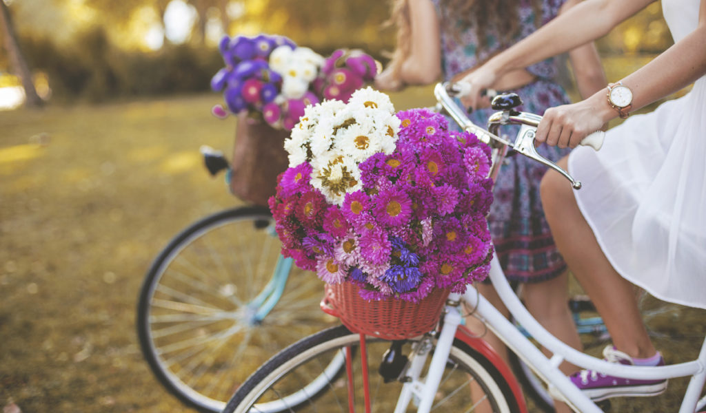 Young woman riding bike with basket of flowers
