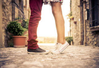 Young couple at sunset, girls stands on tiptoe to kiss man - Close up on shoes