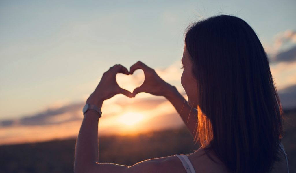 Girl making heart symbol with her hands in sunset