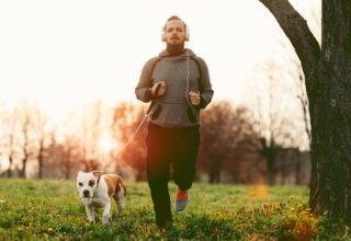 Man jogging with his dog while listening to music