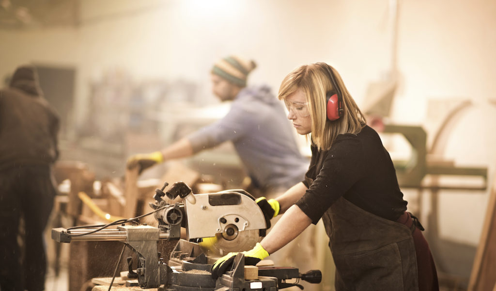 Woman operating on circular saw in workshop
