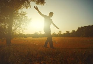 Man walking on tightrope in meadow with sunset