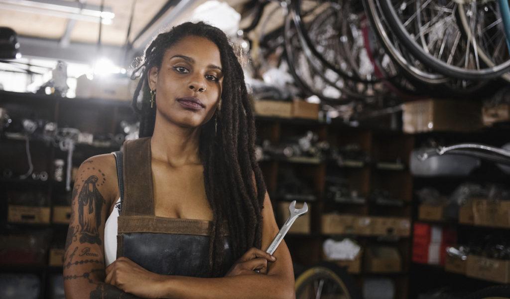Female bicycle mechanic in bike repair workshop