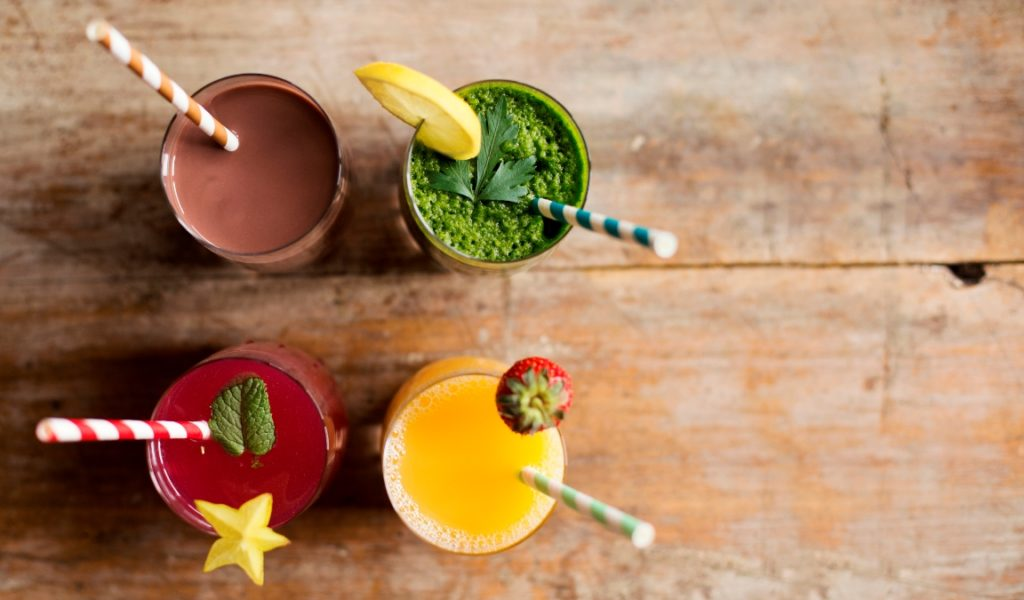Birdseye view of four smoothies on a table
