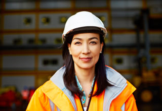 Portrait of a woman in workwear standing on a commercial dock