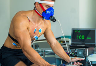 Side view of young adult man having a VO2 test with a VO2 mask on her face, electrocardiogram pads attached, pulse rate 168 BPM, computer recording, indoor bicycle