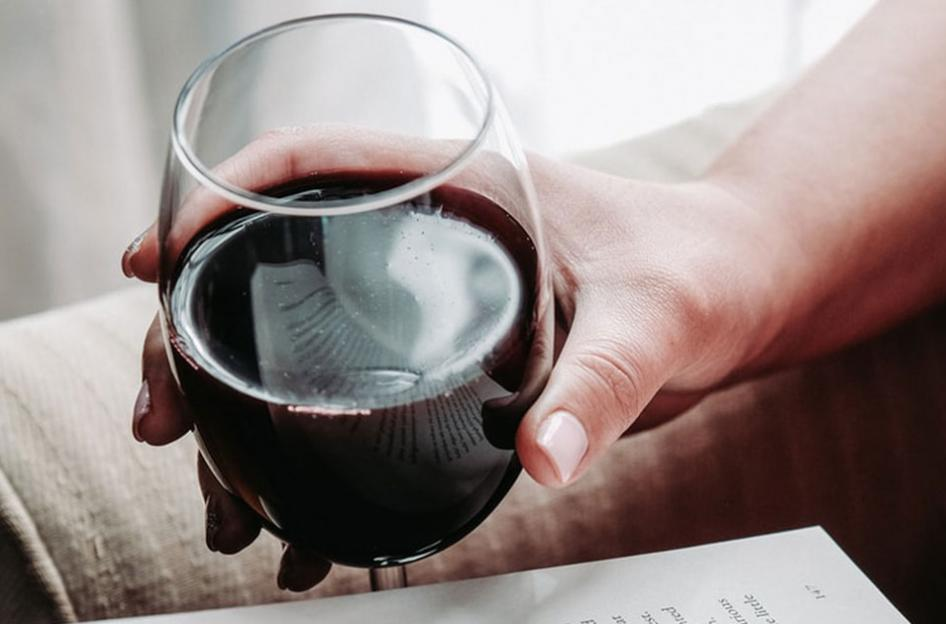 A person holding glass of wine