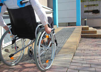 Lady In Wheelchair Going Up Ramp