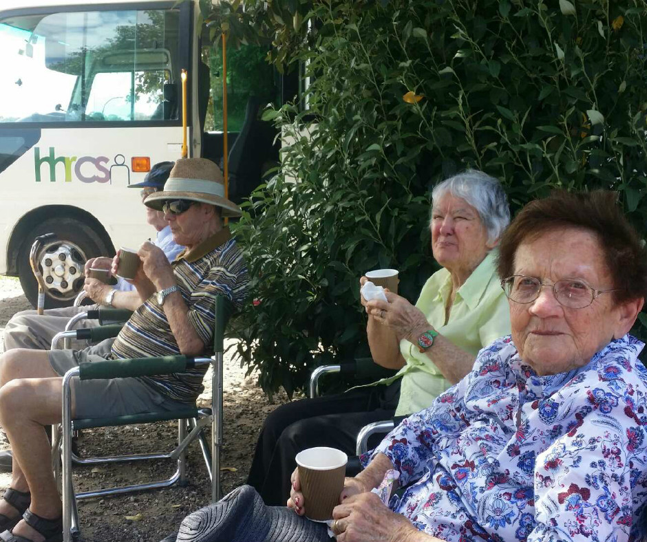 Photo of a group of older people relaing and drinking coffee outside