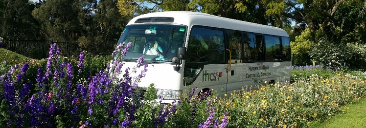 Photo of the HHRCS bus parked in a park with many flowers around