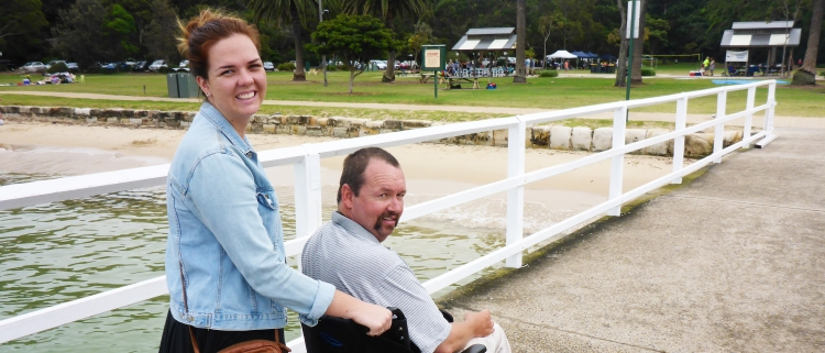 Photo of a young lady  with a man on a wheelchair
