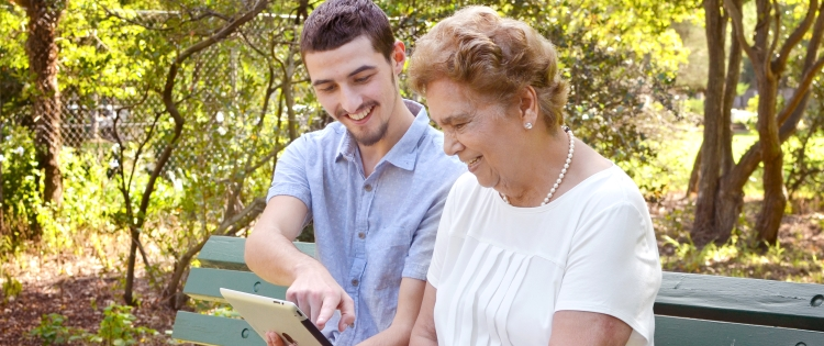 Photo of a young man showing an IPad to a old lady