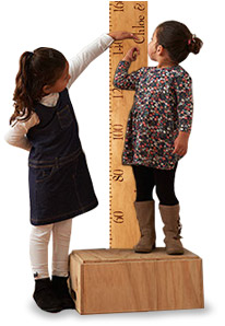 Girls measuring height on growth chart