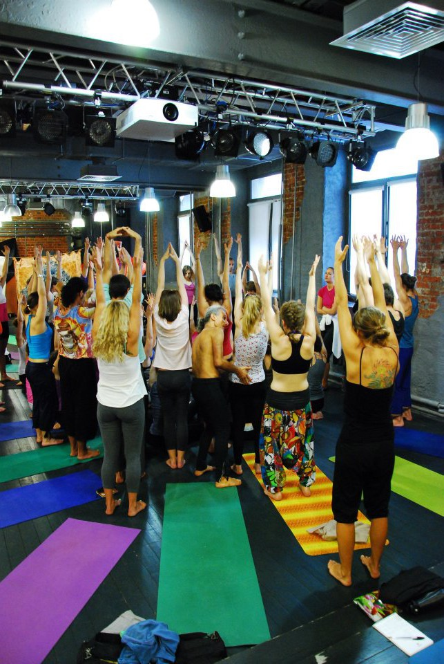 Figure 1: Here we are all lengthening our spine and facilitating calm breathing into the chest by elevating our shoulder blades with our arms above our heads. Photo of my workshop in Moscow by Mikhail Lisov