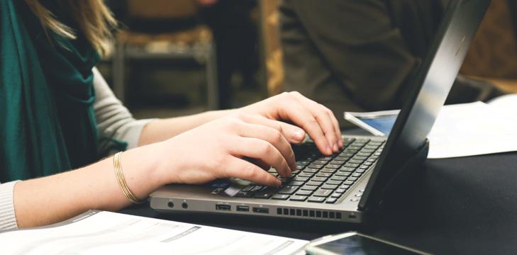 women taking notes on laptop