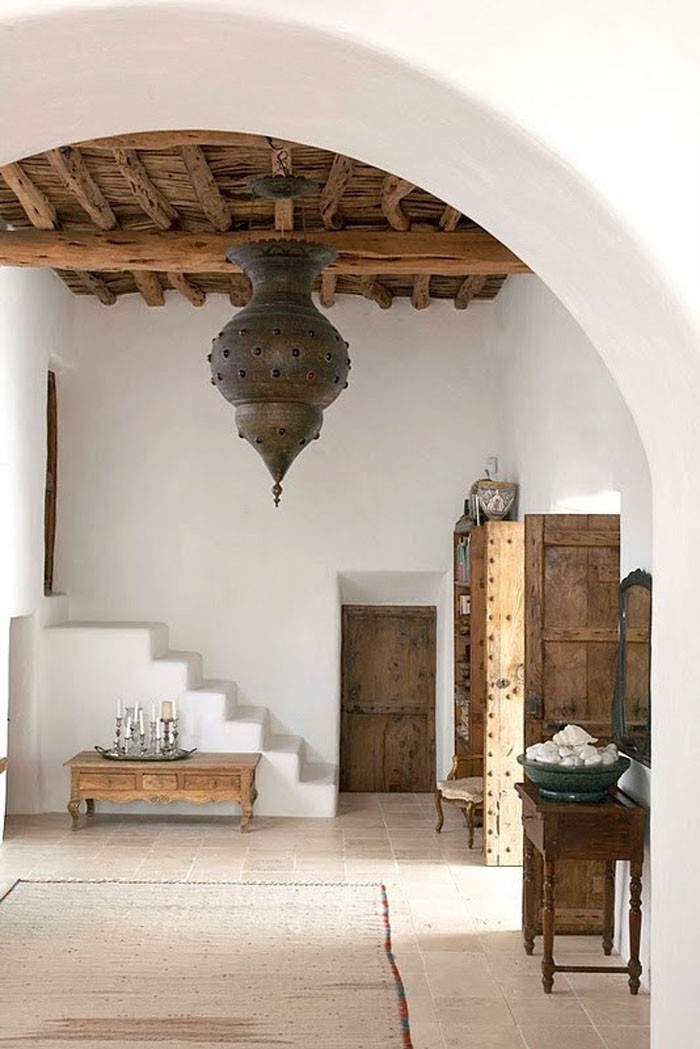 Moroccan style foyer with bolted raw timber doors and furniture