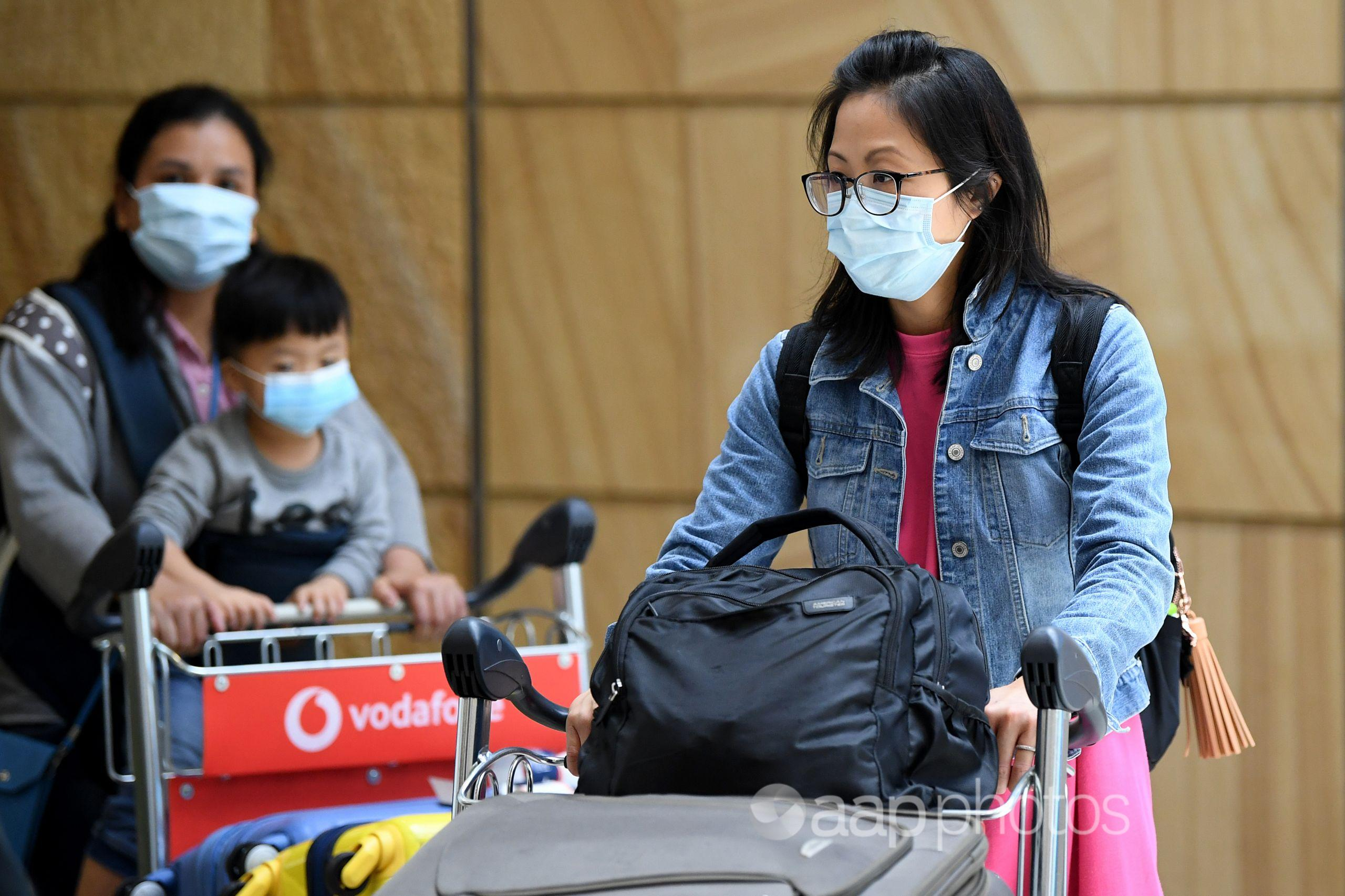 Woman in mask pushes luggage trolley at airport.
