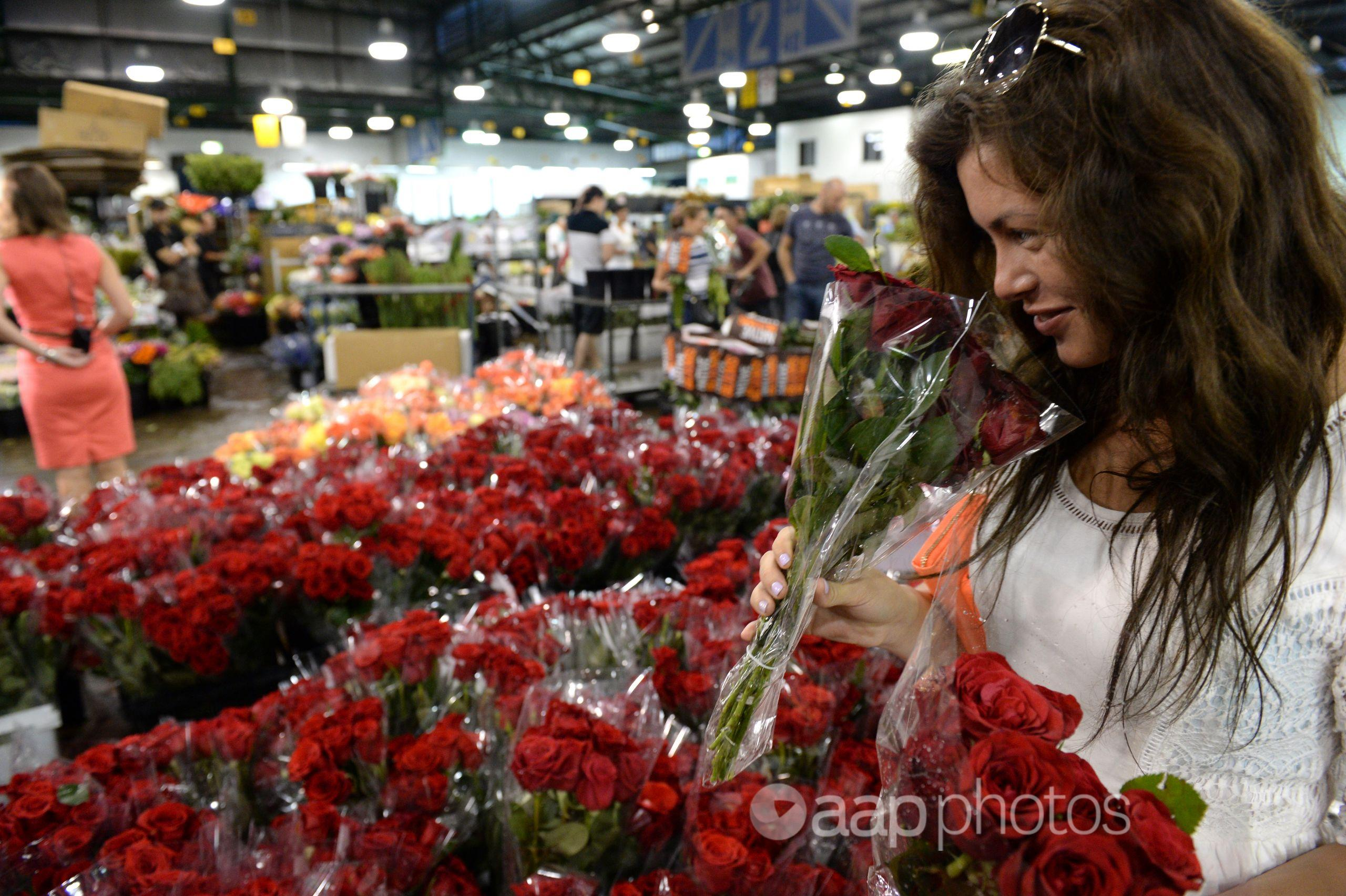 A woman buys roses at the Sydney Flower Market in Sydney.