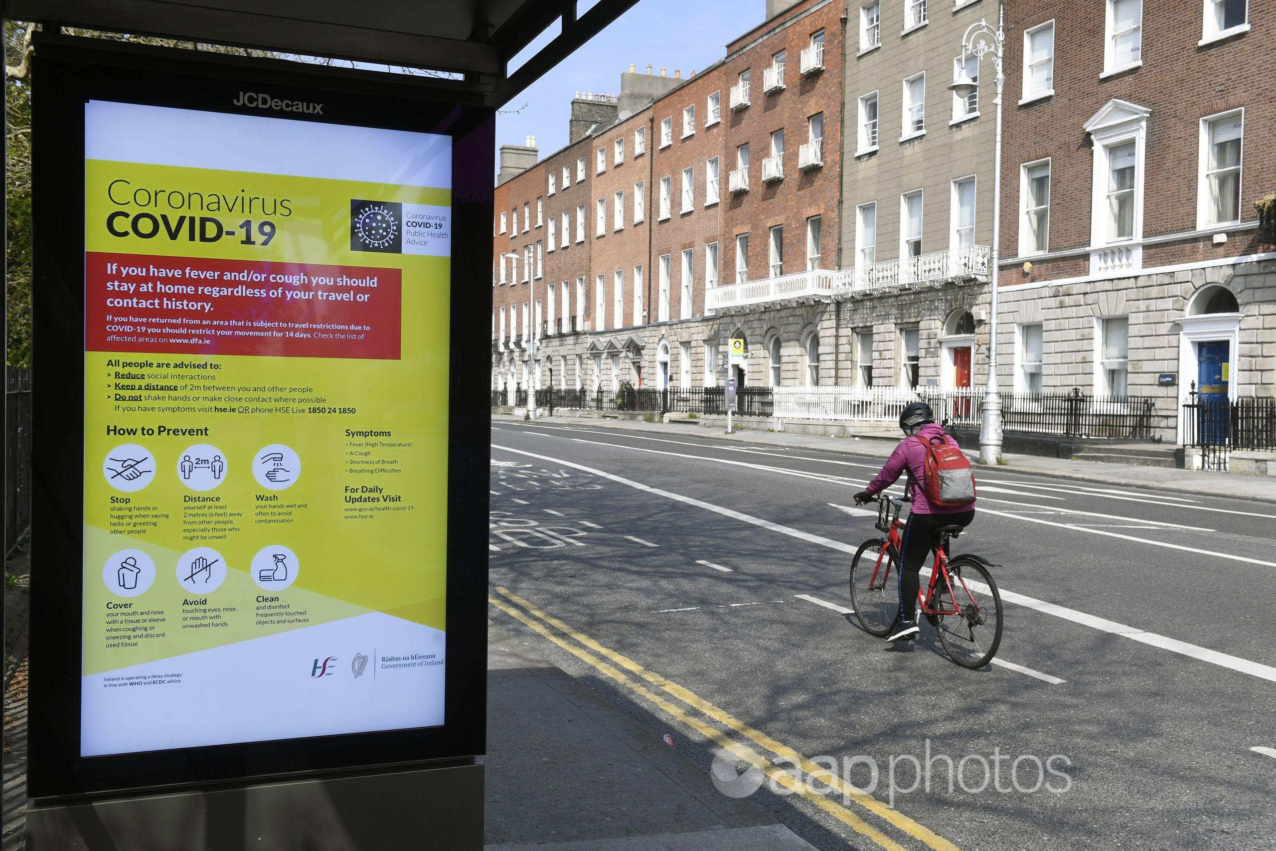 A cyclist passes a bus stop with a COVID-19 health warning in Dublin.
