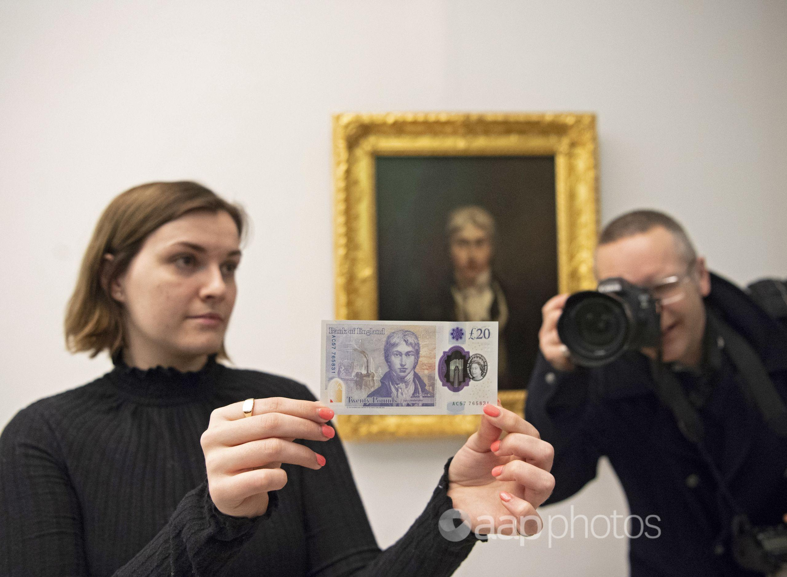 A Tate Britain employee poses with the 20 pound note.