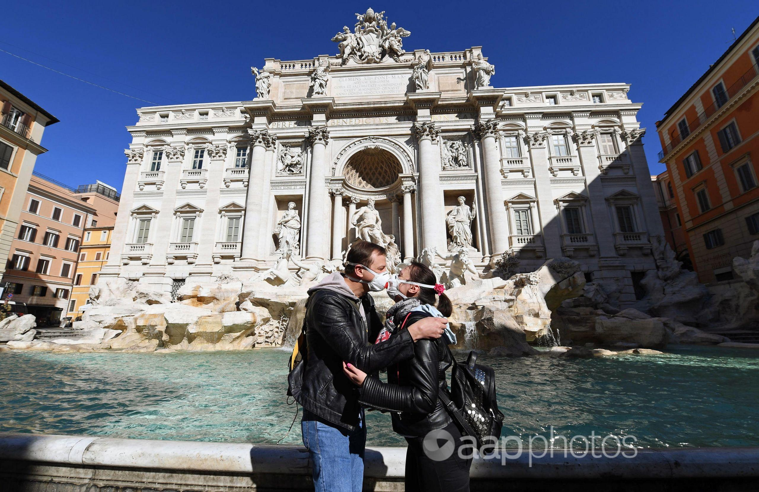 Tourists kiss in front of the Fontana di Trevi in Rome.